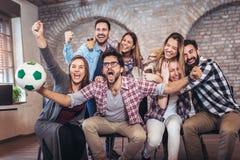 Amici o tifosi felici che guardano calcio sulla TV e che celebrano vittoria fotografie stock