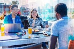 Amici positivi che hanno tempo splendido nel caffè Fotografia Stock Libera da Diritti