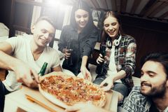 Amici sedersi e bere e raggiungere per pizza immagini stock libere da diritti