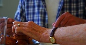 Amici senior che mangiano prima colazione sul tavolo da pranzo 4k video d archivio