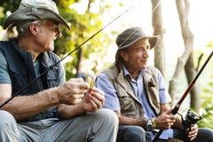 Amici senior che pescano dal lago immagini stock libere da diritti