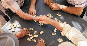 Amici senior che stringono le mani che vincono gioco di domino Fotografia Stock Libera da Diritti