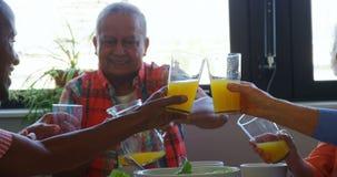 Amici senior che tostano i vetri di succo sul tavolo da pranzo 4k video d archivio