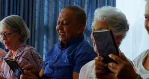 Amici senior felici che utilizzano compressa digitale nel salone 4k video d archivio