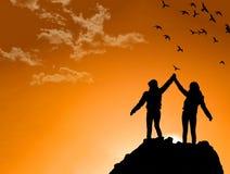 Amici sopra una montagna che stringono le mani sollevate Immagini Stock