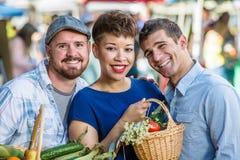 Amici sorridenti al mercato degli agricoltori Fotografia Stock Libera da Diritti