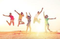 Amici sorridenti che ballano e che saltano sulla spiaggia Fotografia Stock Libera da Diritti