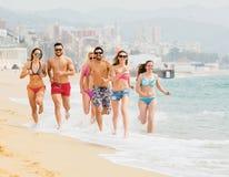 Amici sorridenti che corrono nello swimwear Fotografie Stock