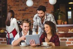 Amici sorridenti che esaminano compressa digitale Fotografia Stock