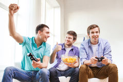 Amici sorridenti che giocano i video giochi a casa Immagini Stock Libere da Diritti