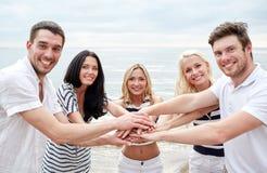 Amici sorridenti che mettono le mani sopra a vicenda Fotografie Stock Libere da Diritti
