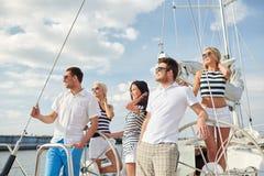 Amici sorridenti che navigano sull'yacht Immagini Stock