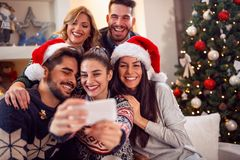 Amici sorridenti che prendono foto con il telefono cellulare per il Natale Immagine Stock