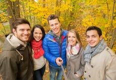 Amici sorridenti che prendono selfie nel parco di autunno Fotografie Stock Libere da Diritti
