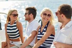Amici sorridenti che si siedono sulla piattaforma dell'yacht Immagine Stock
