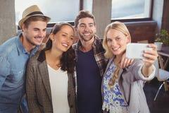 Amici sorridenti che stanno e che prendono i selfies Fotografia Stock Libera da Diritti