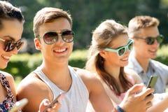 Amici sorridenti con gli smartphones che si siedono nel parco Fotografie Stock Libere da Diritti