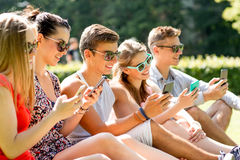 Amici sorridenti con gli smartphones che si siedono sull'erba Immagine Stock Libera da Diritti
