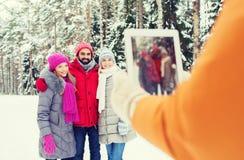 Amici sorridenti con il pc della compressa nella foresta di inverno Immagini Stock Libere da Diritti