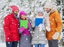Amici sorridenti con il pc della compressa nella foresta di inverno Fotografie Stock