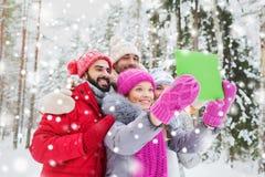 Amici sorridenti con il pc della compressa nella foresta di inverno Fotografia Stock