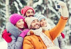 Amici sorridenti con la macchina fotografica nella foresta di inverno Fotografia Stock Libera da Diritti