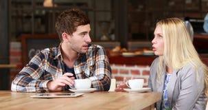 Amici sorridenti dei pantaloni a vita bassa che mangiano un caffè stock footage
