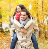 Amici sorridenti divertendosi nel parco di autunno Immagini Stock