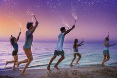 Amici sorridenti felici che corrono alla spiaggia con le candele scintillanti Fotografia Stock Libera da Diritti