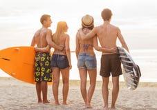 Amici sorridenti in occhiali da sole con le spume sulla spiaggia Fotografia Stock Libera da Diritti