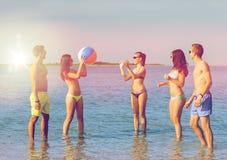 Amici sorridenti in occhiali da sole sulla spiaggia di estate Immagini Stock Libere da Diritti