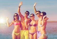 Amici sorridenti in occhiali da sole sulla spiaggia di estate Fotografie Stock