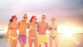 Amici sorridenti in occhiali da sole sulla spiaggia di estate Fotografia Stock