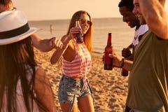 Amici spensierati che bevono birra al partito della spiaggia immagini stock libere da diritti