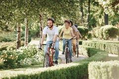 Amici sportivi svegli che guidano le bici in parco Fotografie Stock