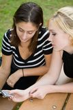 Amici sul telefono cellulare insieme (bella giovane bionda e Brune immagine stock