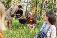 Amici svegli che preparano barbecue in natura Immagine Stock