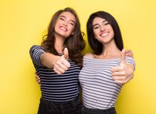 Amici svegli delle donne che mostrano i pollici su su fondo giallo fotografia stock