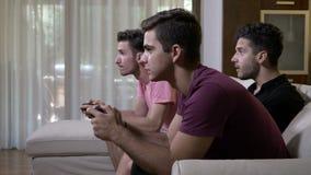 Amici teenager che si siedono su uno strato che spende tempo che gioca un gioco di partita sulla console facendo uso dei regolato stock footage
