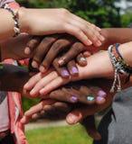 Amici teenager multirazziali che si prendono per mano insieme nella cooperazione Fotografia Stock Libera da Diritti