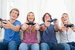 Amici tutti che giocano insieme i video giochi Fotografia Stock