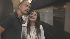 Amici, uomo e donna, coppie, aspettanti nel sottopassaggio, il treno che ha una conversazione e che guarda in direzione di stock footage