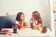 Amicizia di piccole sorelle in aula al giorno di conoscenza Le bambine mangiano la mela all'intervallo di pranzo bambini annoiati fotografia stock