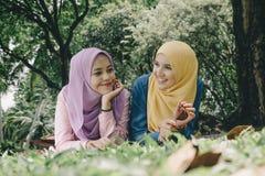 Amicizia e concetto di felicità ritratto delle giovani donne di sorriso che mettono su erba Fotografie Stock
