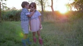 Amicizia, segreto di sussurro del ragazzo nell'orecchio della ragazza del bambino sul tramonto del fondo video d archivio