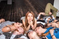 Amicizia, svago, estate e concetto della gente - gruppo di amici sorridenti che si trovano sul pavimento nel cerchio all'interno immagine stock