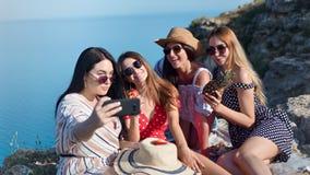 Amico alla moda sorridente della donna di viaggio che gode prendendo selfie al fondo della montagna del mare archivi video