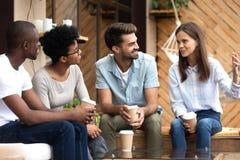 Amico che ascolta la ragazza che si siede insieme in caffè bevente del caffè fotografia stock libera da diritti
