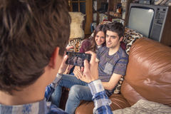 Amico che prende le foto alle coppie adolescenti su un sofà Immagine Stock