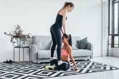 Amico d'aiuto della donna in gamba che allunga allenamento a casa Fotografie Stock Libere da Diritti